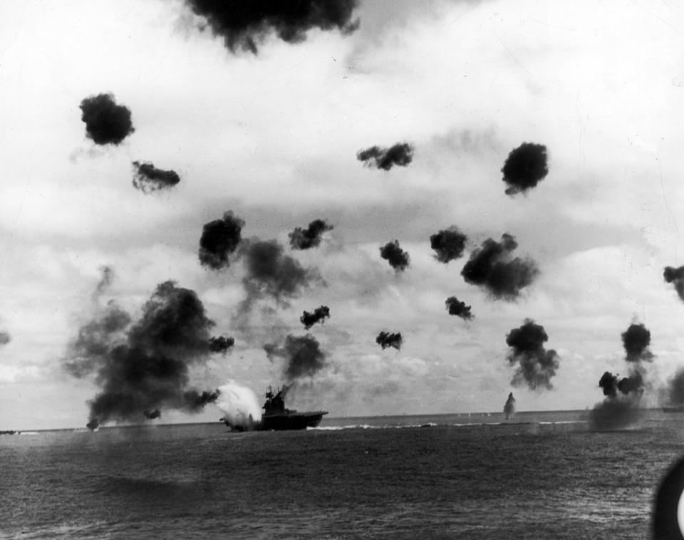 Smoke from antiaircraft guns fills the sky as aircraft carrier USS Yorktown (rear, C) is hit by a Japanese torpedo during the Battle of Midway on June 6, 1942. | US Navy/The LIFE Picture Collection—Getty Images