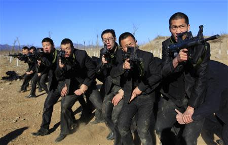 Students holding replica 95 semi-automatic rifles practice protecting their employers at a shooting training field managed by the military during the Tianjiao Special Guard/Security Consultant training on the outskirts of Beijing