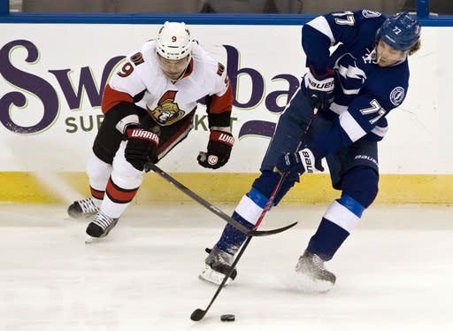 Ottawa Senators' Milan Michalek (9) pressures Tampa Bay Lightning's Victor Hedman (77) during the first period of an NHL hockey game on Thursday, Dec. 5, 2013 in Tampa, Fla. (AP Photo/Steve Nesius)