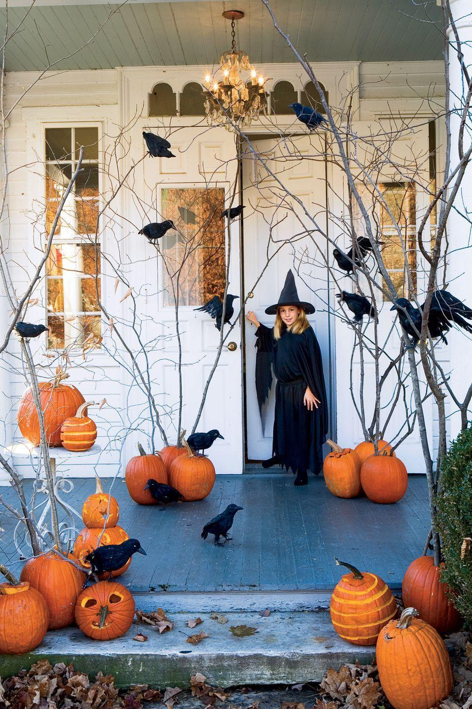 """<p>For a killer entrance, perch artificial <span class=""""redactor-unlink"""">ravens</span> on tall branches with pumpkins as their base. </p>"""
