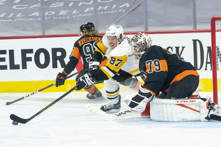 Pittsburgh Penguins' Sidney Crosby, left, reaches for the puck in front of Philadelphia Flyers goaltender Carter Hart, right, during the first period of an NHL hockey game, Friday, Jan. 15, 2021, in Philadelphia. (AP Photo/Chris Szagola)