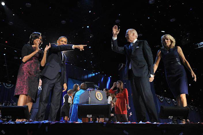 US President Barack Obama, flanked by First Lady Michelle Obama, points to his partner Vice-President Joe Biden, followed by Second Lady Jill Biden following his victory speech on election night November 6, 2012 in Chicago, Illinois. President Barack Obama swept to re-election Tuesday, forging history again by transcending a slow economic recovery and the high unemployment which haunted his first term to beat Republican Mitt Romney. AFP PHOTO/Jewel Samad        (Photo credit should read JEWEL SAMAD/AFP/Getty Images)
