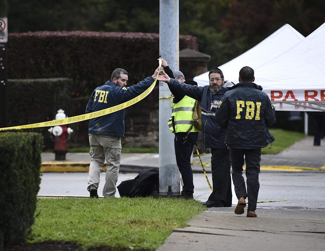 <p>Members of the FBI and others survey the area on Oct. 28, 2018 outside the Tree of Life Synagogue after a shooting there left 11 people dead in the Squirrel Hill neighborhood of Pittsburgh on Oct. 27, 2018. (Photo: Brendan Smialowski/AFP/Getty Images) </p>