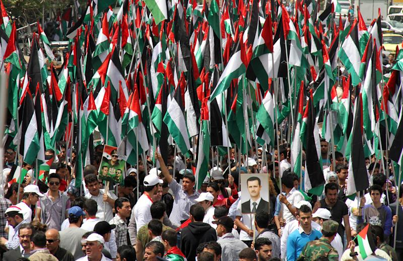Pro-Syrian government demonstrators hold Baath party flags and a picture of President Bashar Assad at a rally at Sabe Bahrat Square to commemorate the 65th anniversary of the foundation of the Ruling Baath Arab Socialist Party in Damascus, Syria, Saturday, April 7, 2012.  Syrian President Bashar Assad has accepted a cease-fire deadline brokered by international envoy Kofi Annan, which calls for his forces to pull out of towns and cities by Tuesday and for both government and rebels to lay down their arms by 6 a.m. local time Thursday.(AP Photo Bassem Tellawi)