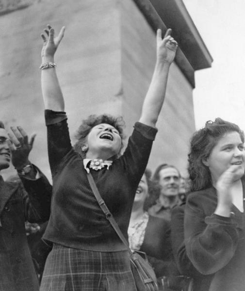 FILE - In this Aug. 25, 1944 file photo, a Parisian girl hold her hands high in the victory sign as American troops pass through Paris, on their way to the front after the French capital was liberated. The fighting for the liberation of Paris took place from August 19 to August 25, 1944. (AP Photo/Richard Boyer, File)