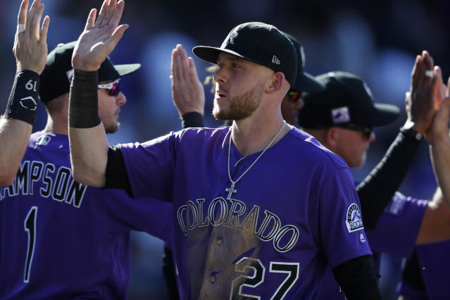 Colorado Rockies shortstop Trevor Story is congratulated by teammates after the ninth inning of a baseball game against the Arizona Diamondbacks, Thursday, Sept. 13, 2018, in Denver. (AP Photo/David Zalubowski)