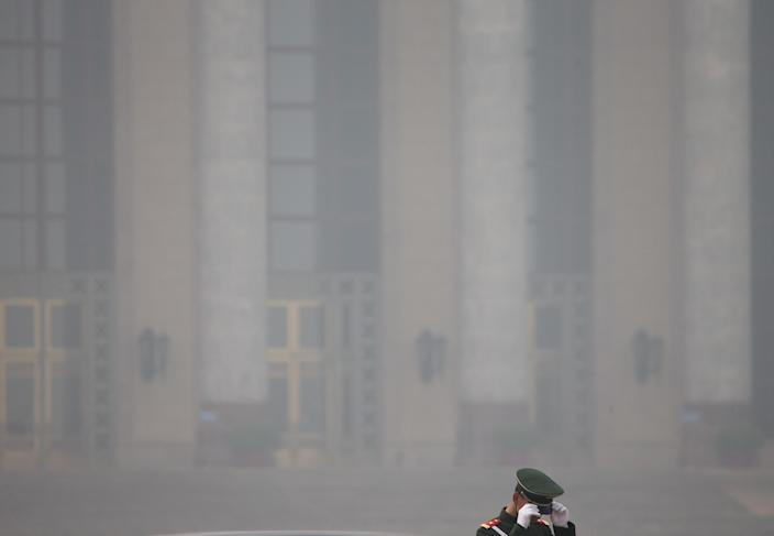 FILE - In this March 8, 2013 file photo, a Chinese paramilitary policeman adjusts his hat against the Great Hall of the People, on a polluted day, before a plenary session of the National People's Congress in Beijing. While the numbers are hard to quantify, executive recruitment consultants say they are noticing that it is becoming harder to attract top talent to China - both expats and Chinese nationals educated abroad. If the polluted skies continue, companies may have to fork out more money for their workers, settle for less qualified candidates or hire local workers instead of expats. (AP Photo/Andy Wong, File)