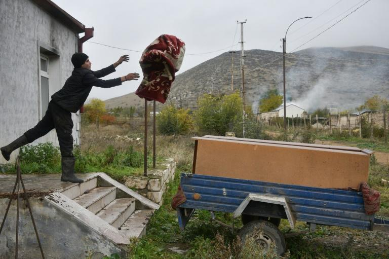 An Armenian man throws a carpet into a car trailer as he leaves the village of Nor-Karmiravan outside Agdam, before the territory was returned to Azerbaijan