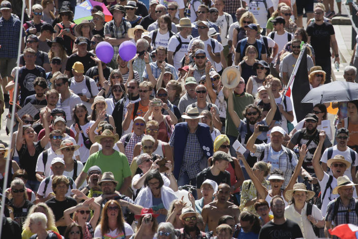 People mostly without face masks attend a demonstration with the slogan 'The end of the pandemic - freedom day' - against coronavirus restrictions in Berlin, Germany, Saturday, Aug. 1, 2020. It comes amid increasing concern about an upturn in infections in Germany. (AP Photo/Markus Schreiber)