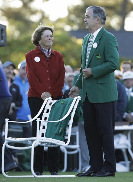 """Billy Payne, chairman of Augusta National Golf Club, with Kathleen """"Kit"""" Gawthrop, wife of Arnlold Palmer, place a green jacket on a chair to honor Arnold Palmer before the first round for the Masters golf tournament Thursday, April 6, 2017, in Augusta, Ga. (AP Photo/David J. Phillip)"""