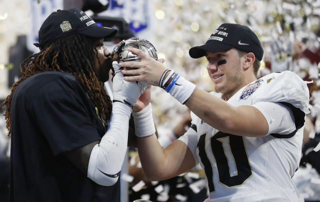"Central Florida linebacker <a class=""link rapid-noclick-resp"" href=""/ncaaf/players/228732/"" data-ylk=""slk:Shaquem Griffin"">Shaquem Griffin</a>, left, kisses the championship trophy as Central Florida quarterback McKenzie Milton looks on after the Peach Bowl NCAA college football game against Auburn, Monday, Jan. 1, 2018, in Atlanta. Central Florida won 34-27. (AP Photo/John Bazemore)"