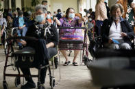 FILE - In this Jan. 12, 2021, file photo, Resident Sabeth Ramirez, 80, center, waits in line with others for the Pfizer-BioNTech COVID-19 vaccine at the The Palace assisted living facility in Coral Gables, Fla. Governors and health officials have been reluctant to sign on to a Biden administration plan to open 100 federally supported vaccination sites by the end of February. With vaccine supplies running tight, they want assurances that the doses will come from a separate federal supply and not their own. (AP Photo/Lynne Sladky, File)