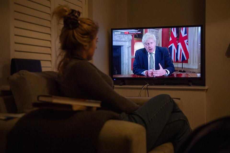 A woman watches Prime Minister Boris Johnson making a televised address to the nation from 10 Downing Street, London, setting out new emergency measures to control the spread of coronavirus in England.