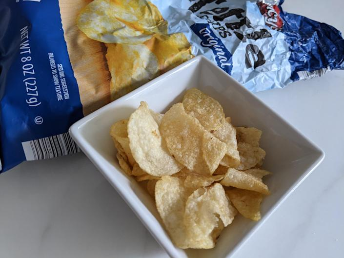 Aldi kettle chips in a small white bowl with the blue original bag in the back