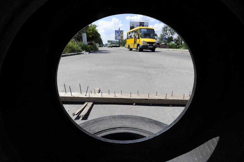 A photo taken through a tyre shows a minibus driving past a checkpoint in Makiivka, 15 kilometers east of Donetsk, on July 11, 2014