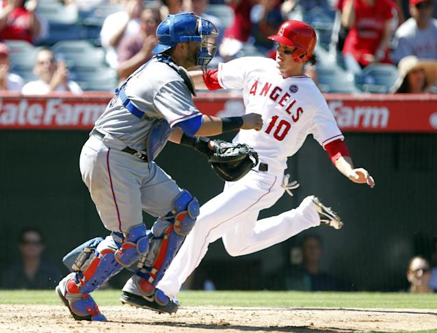 Los Angeles Angels' Grant Green, right, scores as the throw to Texas Rangers catcher Geovany Soto goes wide right on a two-run double by Angels' Andrew Romine in the fourth inning during a baseball game, Sunday, Sept. 8, 2013, in Anaheim, Calif. (AP Photo/Alex Gallardo)