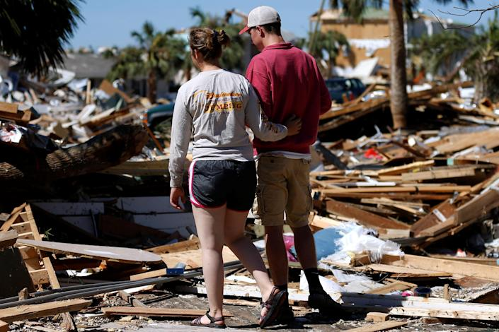 <p>Parker Miller and her boyfriend Corey Sykes walk through debris caused by Hurricane Michael in Mexico Beach, Fla., Oct. 12, 2018. (Photo: Jonathan Bachman/Reuters) </p>