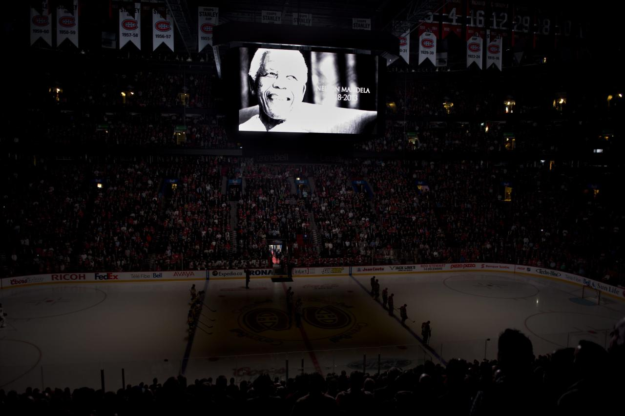 A moment of silence for Nelson Mandela is observed prior to the Montreal Canadiens and Boston Bruins NHL hockey game in Montreal on Thursday, Dec. 5, 2013. (AP Photo/The Canadian Press, Paul Chiasson)