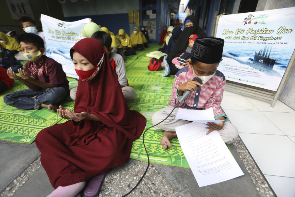 Students pray during a vigil for the crew of Indonesian Navy submarine KRI Nanggala that went missing while participating in a training exercise on Wednesday, at an elementary school in Surabaya, East Java, Indonesia, Friday, April 23, 2021. Indonesian navy ships scoured the waters off Bali on Friday as they raced against time to find the submarine that disappeared two days ago and has less than a day's supply of oxygen left for its 53 crew. (AP Photo/Trisnadi)
