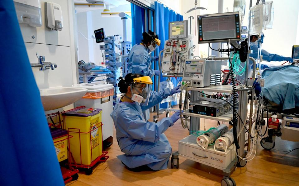 Clinical staff wear personal protective equipment (PPE) while caring for a patient in the Intensive Care unit (ICU) at the Royal Papworth Hospital, in Cambridge, in May 2020 - Neil Hall/EPA