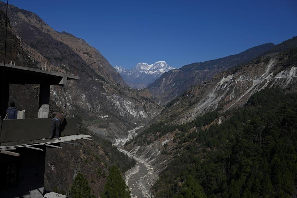 A mason works at an under-construction building site on the edge of the mountain valley in Chamoli district of Uttarakhand (AFP via Getty Images)
