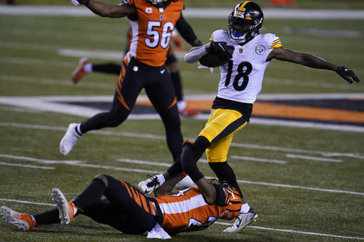 Pittsburgh Steelers' Diontae Johnson (18) is tackled by Cincinnati Bengals' Darius Phillips (23) during the first half of an NFL football game, Monday, Dec. 21, 2020, in Cincinnati. (AP Photo/Michael Conroy)