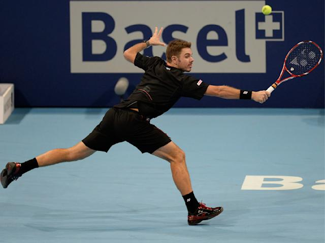 Switzerland's Stanislas Wawrinka returns a ball to Edouard Roger-Vasselin from France during their first round match at the Swiss Indoors tennis tournament at the St. Jakobshalle in Basel, Switzerland, on Tuesday, Oct. 22, 2013. (AP Photo/Keystone,Georgios Kefalas)