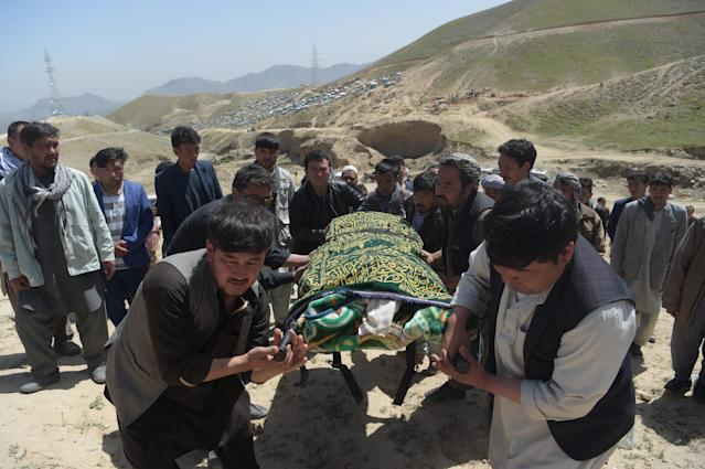 <p>Afghan Shiite mourners carry the coffin of one of the 57 victims of a bomb blast before the burial a day after the attack on a voter registration centre in Kabul, on April 23, 2018. – Hundreds of grieving Afghans buried their loved ones in Kabul on April 23 amid growing anger over a suicide attack on a voter registration centre that killed 57 people including children and wounded over 100. (Photo: Shah Marai/AFP/Getty Images) </p>
