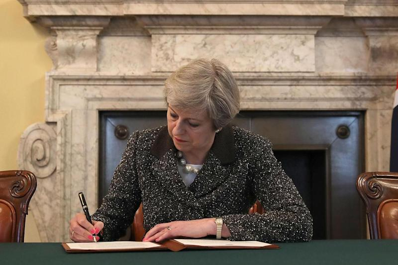 Britain's PM Theresa May signs the official letter to European Council President Donald Tusk, invoking Article 50: AFP/Getty Images