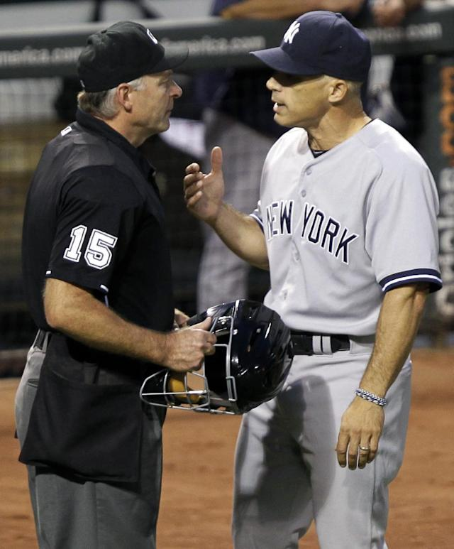 New York Yankees manager Joe Girardi, right, talks to first base umpire Jim Joyce (15) after he had an argument with Baltimore Orioles manager Buck Showalter at the end of the first inning of a baseball game, Monday, Sept. 9 2013, in Baltimore. The Orioles won 4-2. (AP Photo/Luis M. Alvarez)