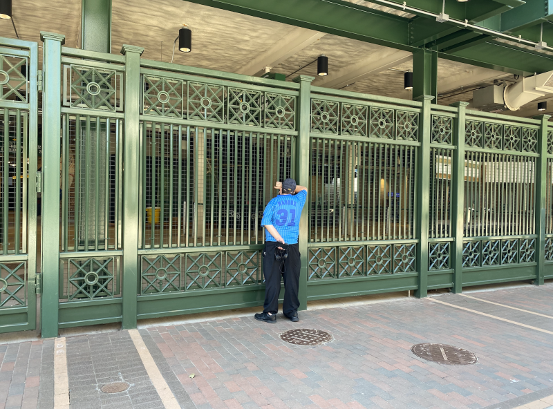 A Cubs fan looks inside Wrigley Field on opening day, where fans were not allowed. (Yahoo Sports)