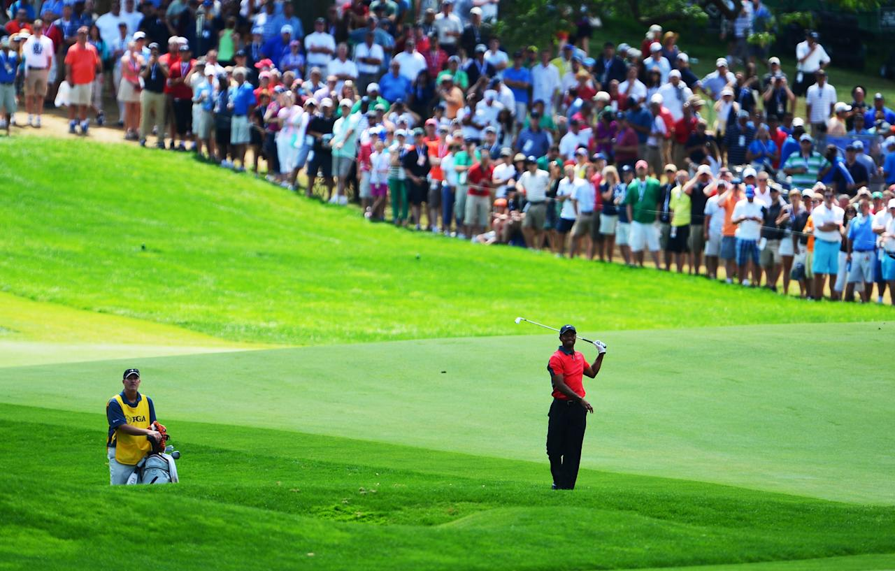 ROCHESTER, NY - AUGUST 11: Tiger Woods of the United States hits an approach shot on the 17th hole as caddie Joe LaCava looks onduring the final round of the 95th PGA Championship on August 11, 2013 in Rochester, New York. (Photo by Stuart Franklin/Getty Images)