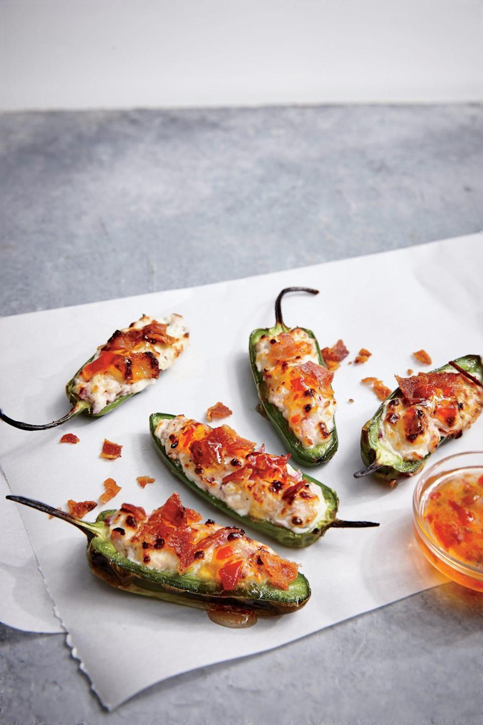 """<p>Salty bacon, <a href=""""https://www.myrecipes.com/ingredients/ways-to-use-goat-cheese"""" rel=""""nofollow noopener"""" target=""""_blank"""" data-ylk=""""slk:rich goat cheese"""" class=""""link rapid-noclick-resp"""">rich goat cheese</a>, savory-sweet jelly, and roasted jalapeño--it takes teamwork to make the dream work. If you already have the grill going, these dreamy little bites are equally easy to cook outdoors.</p>"""