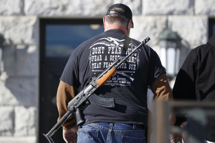FILE - A man carries his weapon during a second amendment gun rally at Utah State Capitol on Feb. 8, 2020, in Salt Lake City. Utah is one of several more states weighing proposals this year that would allow people to carry concealed guns without having to get a permit, a trend supporters say bolsters Second Amendment rights but is alarming to gun-control advocates. (AP Photo/Rick Bowmer, File)