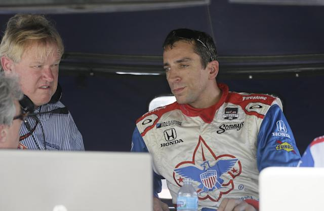 Driver Justin Wilson talks to crew members after a practice session for the IndyCar Detroit Grand Prix auto race on Belle Isle in Detroit, Friday, May 30, 2014. (AP Photo/Carlos Osorio)