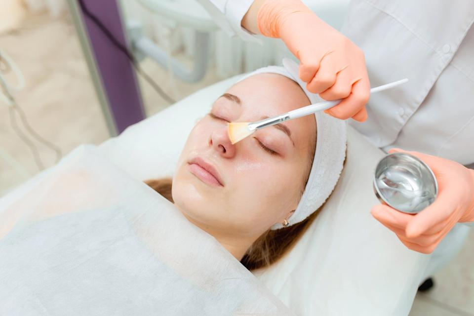 Cosmetologist applying mask on client's face in spa salon. Wellness center. Healthcare occupation