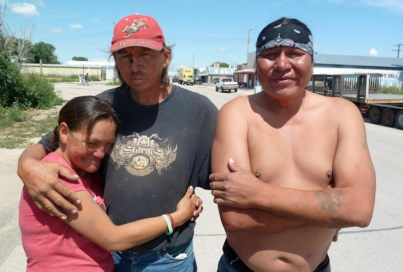 In this Aug. 8, 2013 photo, Crystal Tail, left, Stanley Flying Hawk, center, and Aloysius White Dress in Whiteclay, Neb., are seen where they live in the town's barren streets to avoid arrest on the nearby Pine Ridge Indian Reservation for being drunk. A special election is being held Tuesday, Aug. 13, 2013, on whether to end prohibition and allow the tribe to sell alcohol and use the profits for education and detoxification and treatment centers, for which there is currently little to no funding. (AP Photo/Carson Walker)