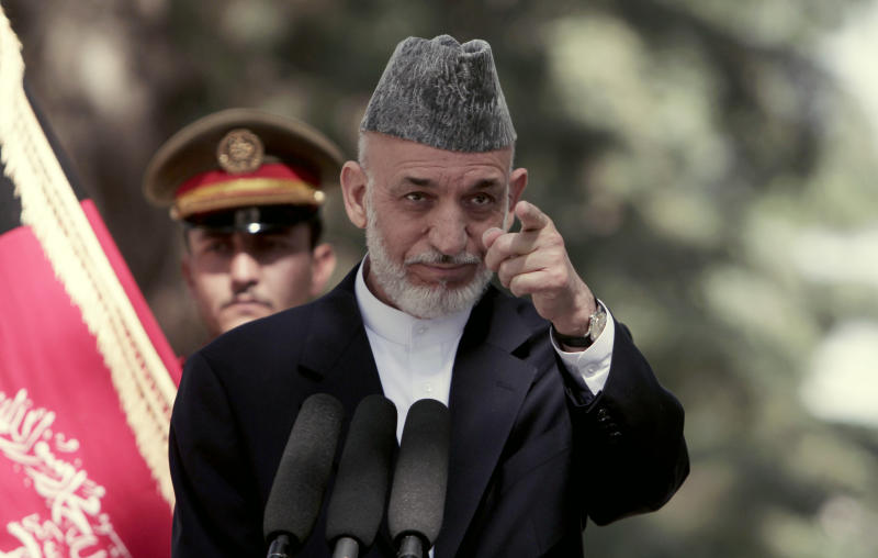 Afghan President Hamid Karzai takes a question during a press conference at the presidential palace in Kabul, Afghanistan, Monday, Oct. 7, 2013. Karzai says disagreements over security and sovereignty are impeding a security deal with the United States and says he will convene a council of elders in one month to discuss the agreement. (AP Photo/Rahmat Gul)