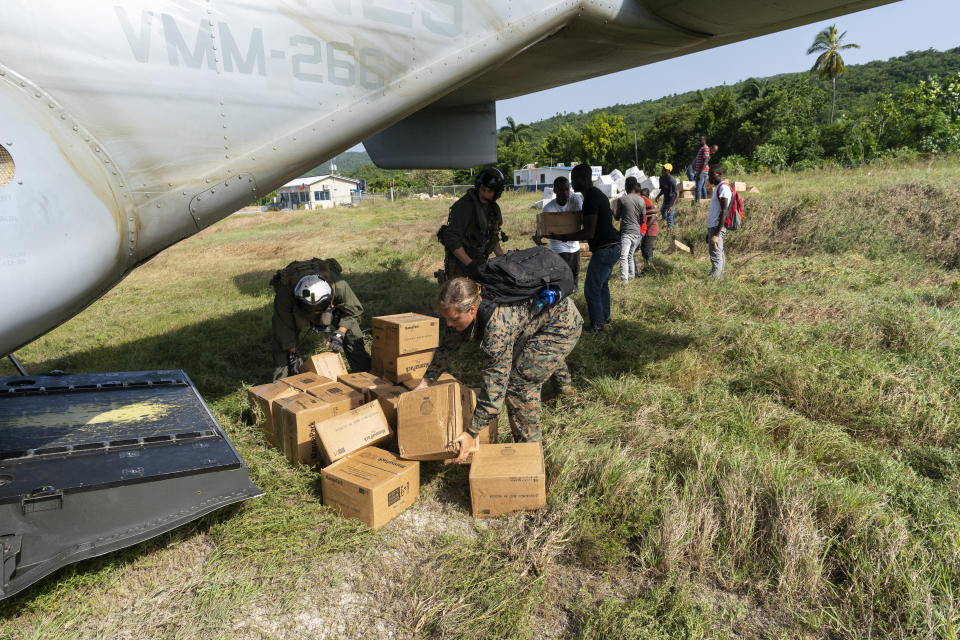 """U.S. Marines and Haitian aid workers unload food from a VM-22 Osprey at Jeremie Airport, Saturday, Aug. 28, 2021, in Jeremie, Haiti. The VMM-266, """"Fighting Griffins,"""" from Marine Corps Air Station New River, from Jacksonville, N.C., are flying in support of Joint Task Force Haiti after a 7.2 magnitude earthquake on Aug. 22, caused heavy damage to the country. (AP Photo/Alex Brandon)"""