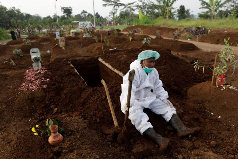 FILE PHOTO: A gravedigger wearing personal protective equipment rests in Indonesia