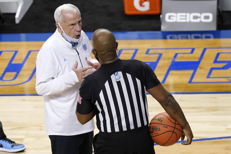 North Carolina head coach Roy Williams talks to a ref during the first half of an NCAA college basketball game against Florida State in the semifinal round of the Atlantic Coast Conference tournament in Greensboro, N.C., Friday, March 12, 2021. (AP Photo/Gerry Broome)