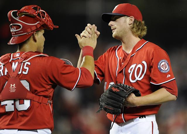 Washington Nationals relief pitcher Ross Detwiler, right, celebrates the team's 8-3 win over the Milwaukee Brewers with catcher Wilson Ramos, following a baseball game, Saturday, July 19, 2014, in Washington. (AP Photo/Nick Wass)