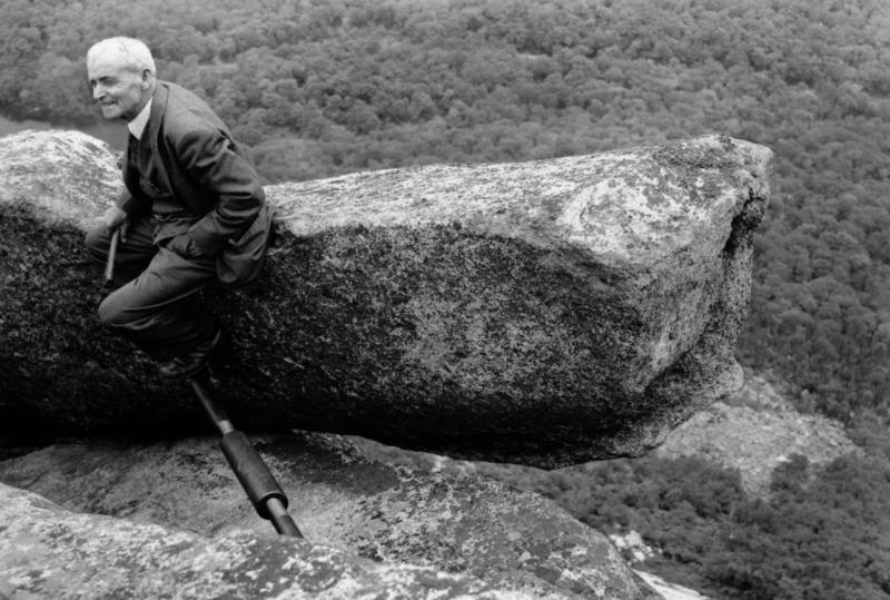 In this photo provided by the Littleton Area Historical Society, Edward Geddes sits on the top of the Old Man of the Mountain profile in this early 1900s photo in Franconia, N.H. Geddes, a stone quarry superintendent from Quincy, Massachusetts, was the first man to do repair work on New Hampshire's iconic figure, which fell nearly ten years ago. (AP Photo/Littleton Area Historical Society)
