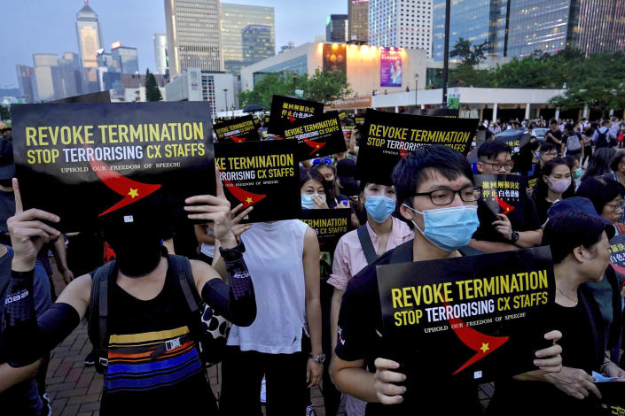 Demonstrators hold signs opposing the recent firings of Cathay Pacific employees as they gather for a demonstration at the Edinburgh Square in Hong Kong, Wednesday, Aug. 28, 2019. Trade union members in Hong Kong are rallying against the city's flagship Cathay Pacific airline for firing employees linked to ongoing pro-democracy protests. (AP Photo/Vincent Yu)