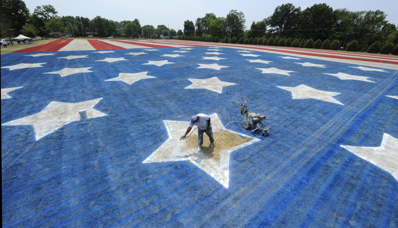 In a Sunday, July 1, 2012 photo, Spud Byrd, of Bowling Green, Ky., paints a star on a 300-foot by 600-foot American flag in the front yard of Robert and Doris Burr's home in Bowling Green, Ky. Burr, with Ken Cardwell, has been pairing the huge flag for 10 years. Cardwell said this year is the last one for the familiar July Fourth sight. (AP Photo/Daily News, Joe Imel)