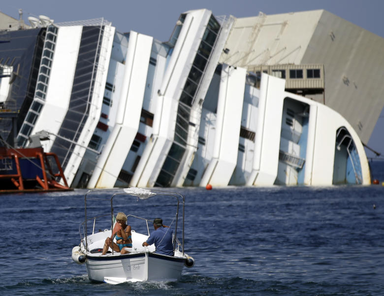 The Costa Concordia cruise ship lies on its side in the Tuscan Island of Isola del Giglio, Monday, July 15, 2013. Salvage crews are working against time to right and remove the shipwrecked Costa Concordia cruise ship, which is steadily compressing down on itself from sheer weight onto its granite seabed perch off the Tuscan island of Giglio. Salvage master Nick Sloane said Monday that the Concordia has compressed some 3 meters (10 feet) since it came to rest on the rocks Jan. 13, 2012 after ramming a jagged reef during a stunt ordered by the captain that cost the lives of 32 people. (AP Photo/Gregorio Borgia)