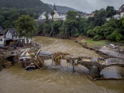 Debris hangs on a damaged bridge over the Ahr River in Schuld, Germany, on Friday, July 16, 2021. Two days before, the river flowed over its banks after strong rain, causing severals deaths and hundreds of people missing. (AP Photo/Michael Probst)