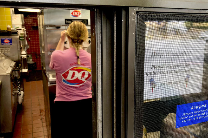 "FILE - In this Sunday, Aug. 19, 2018, file photo a woman prepares a cup of ice cream behind a ""Help Wanted"" sign at a Dairy Queen fast food restaurant in Rutherford, N.J. On Tuesday, Sept. 11, the Labor Department reports on job openings and labor turnover for July. (AP Photo/Ted Shaffrey, File)"