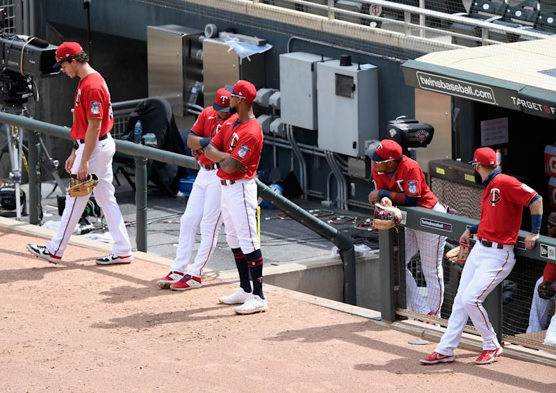 Twins players wait patiently for a drone to complete its mission. (Hannah Foslien/Getty Images)