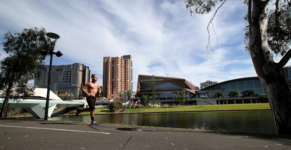 A man runs along the Torrens River in Adelaide.